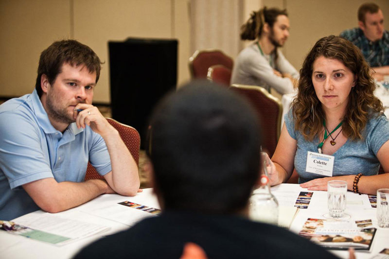 At a conference table full of brochures, a white man and a white woman listen intently to a speaker across the table from them.