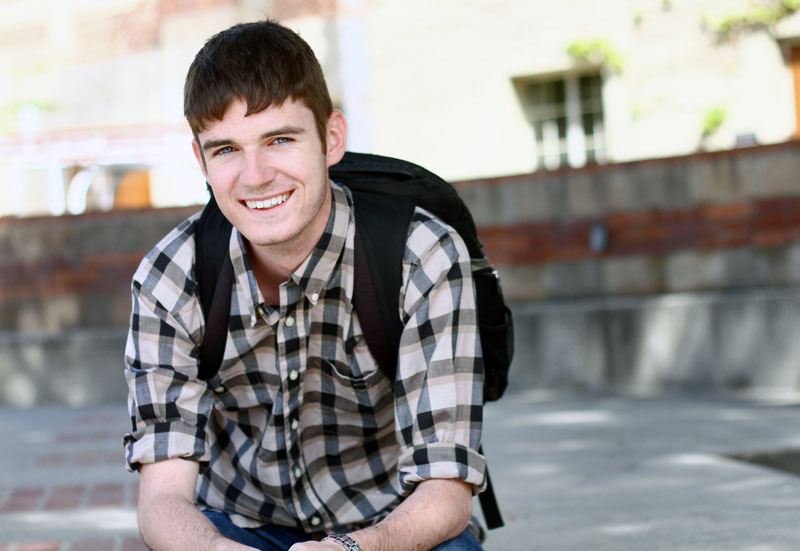 A young white male student smiles at the camera in the campus quad.