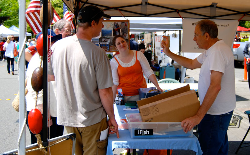A middle aged white man talks with four other adults under a pop up tent and behind a table at a community event.